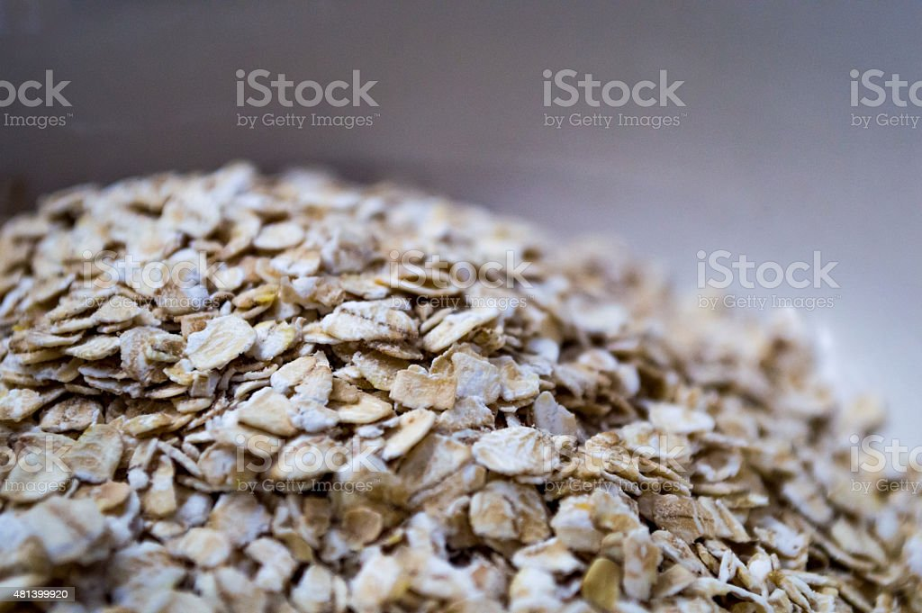 Pile of Dry Rolled Instant Oats in Bowl for Porridge royalty-free stock photo