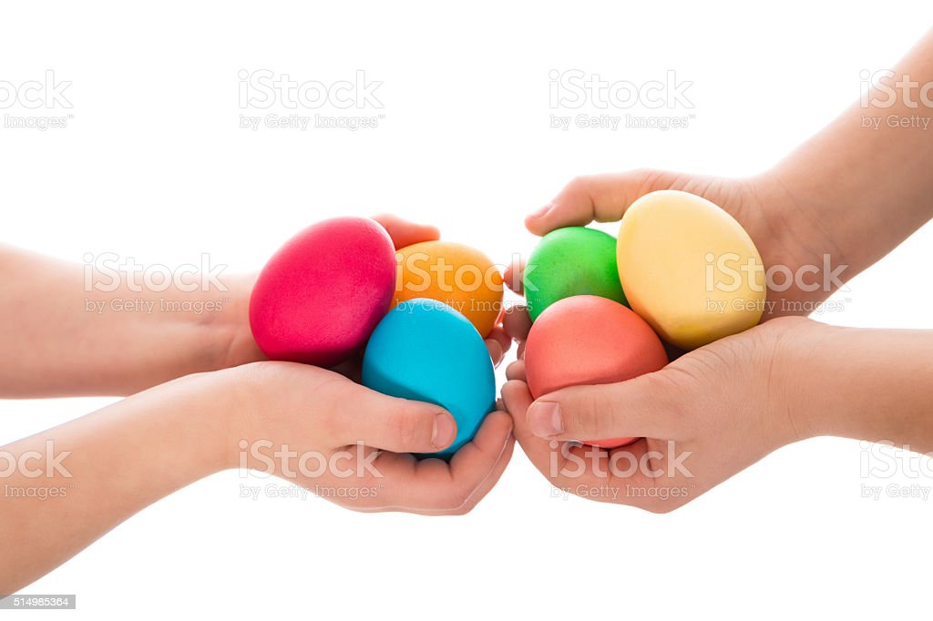 pile of easter eggs in two child hands stock photo