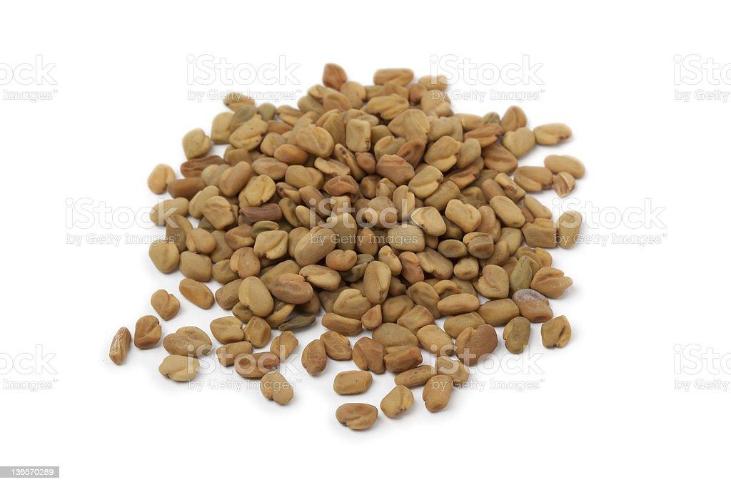 Pile of fenugreek seeds on white background stock photo