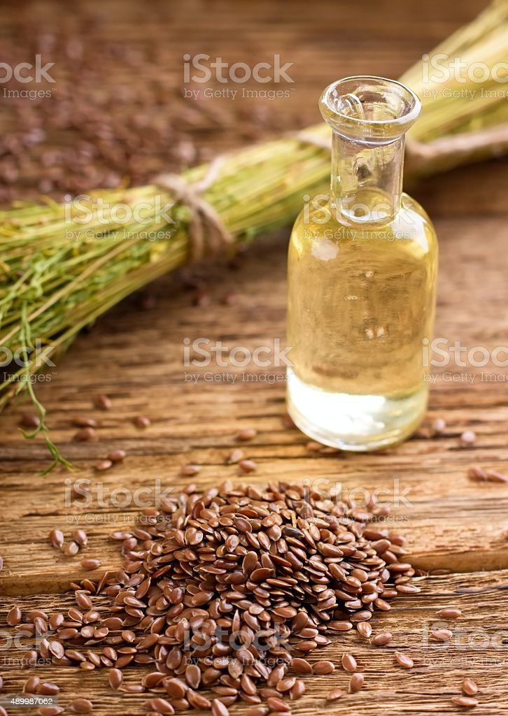 Pile of flax seeds in front of bowl with flaxoil stock photo