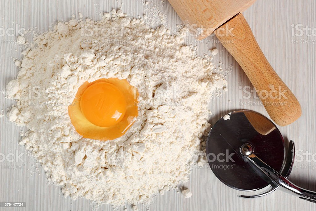 Pile of flour with egg on top stock photo