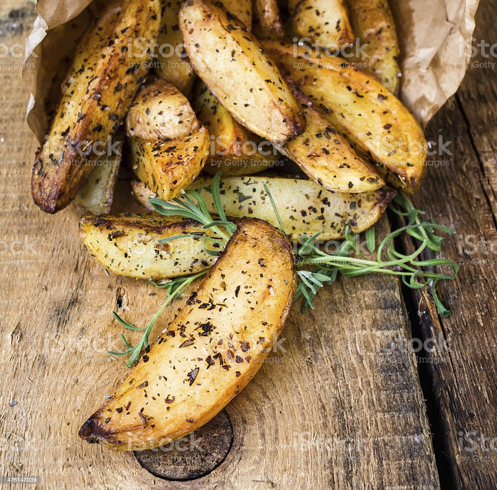 pile of French fries potato wedges with herbs stock photo