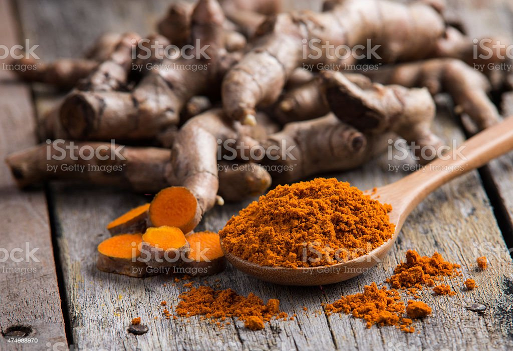 pile of fresh turmeric roots on wooden table stock photo