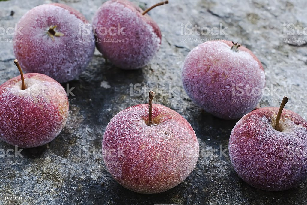 Pile of frosty  red  apples lying on a stone table. royalty-free stock photo