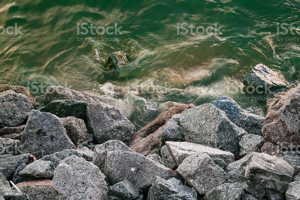 Pile of granite stone at shore stock photo