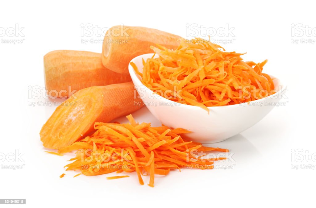 Pile of grated carrots and grater on white background stock photo