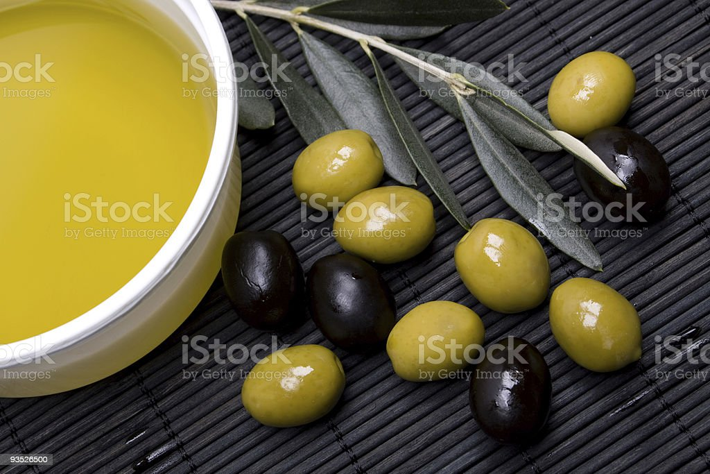 A pile of green and black olives lying next to a bowl of oil stock photo