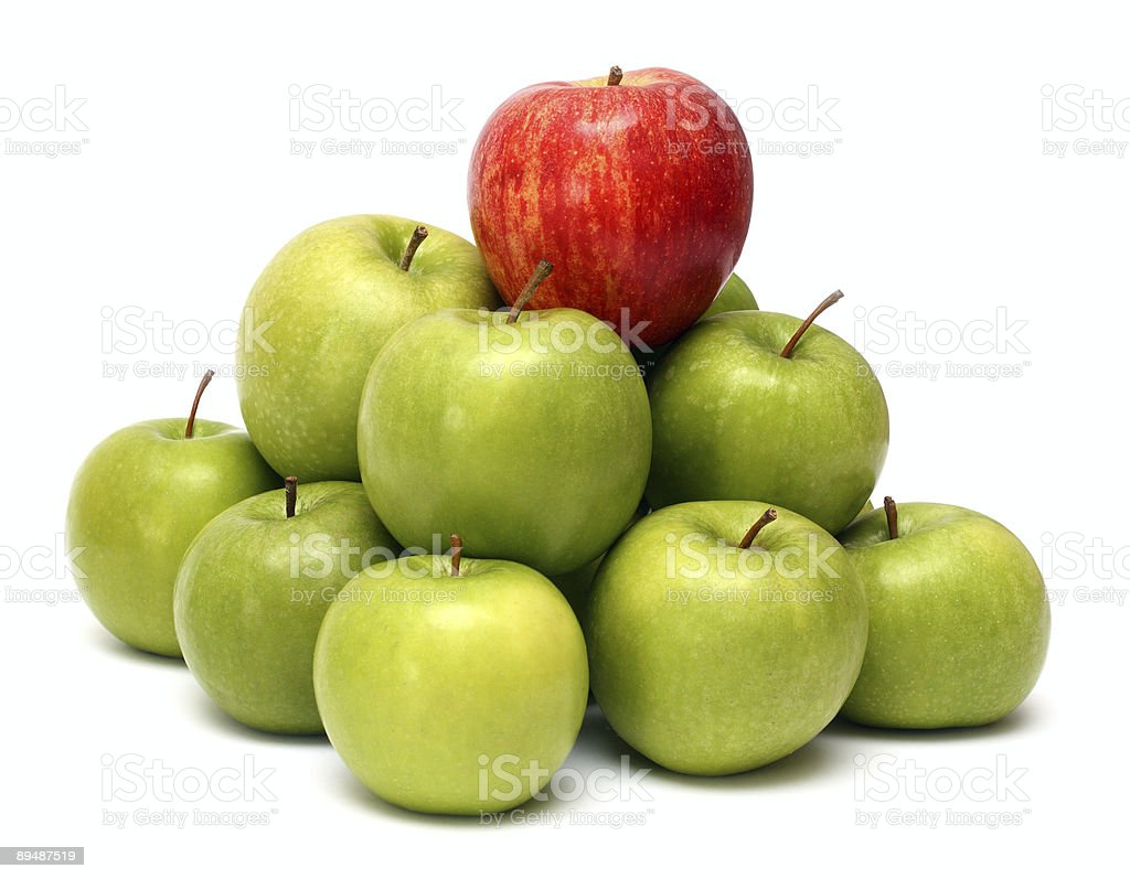 A pile of green apples with a red apple on top stock photo