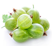 A pile of green gooseberries on a white background