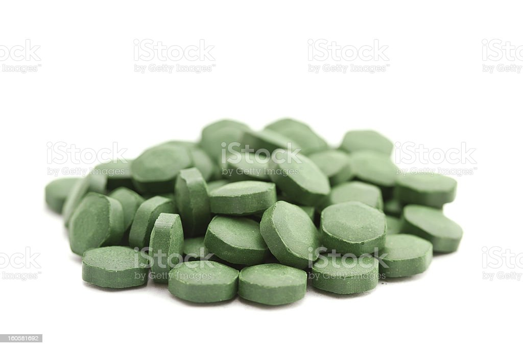 A pile of green spirulina tablets stock photo