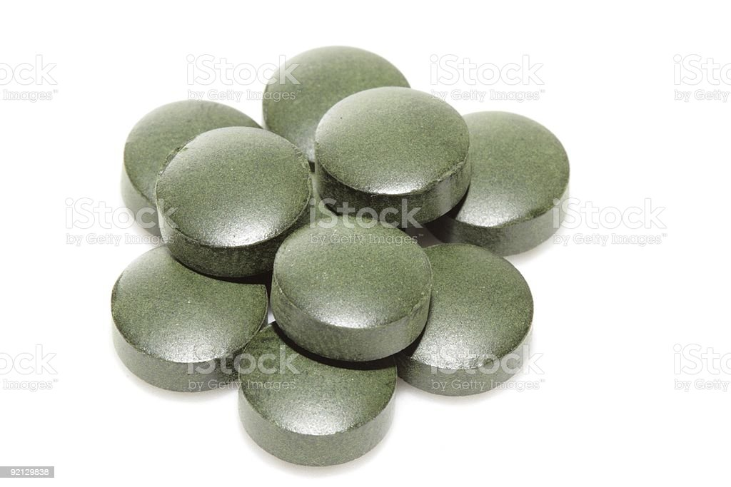 Pile of green spirulina tablets royalty-free stock photo