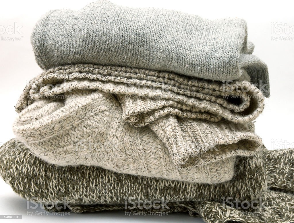 Pile of grey and brown wool clothing on a white background stock photo