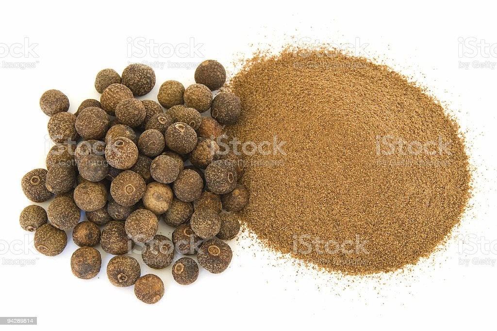 Pile of ground and whole allspice on white royalty-free stock photo