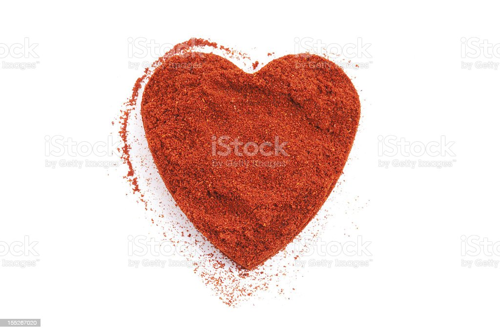 Pile of ground paprika isolated in heart shape on white stock photo