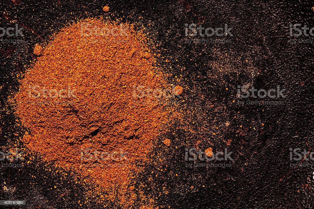 Pile of ground paprika on a textured dark background stock photo