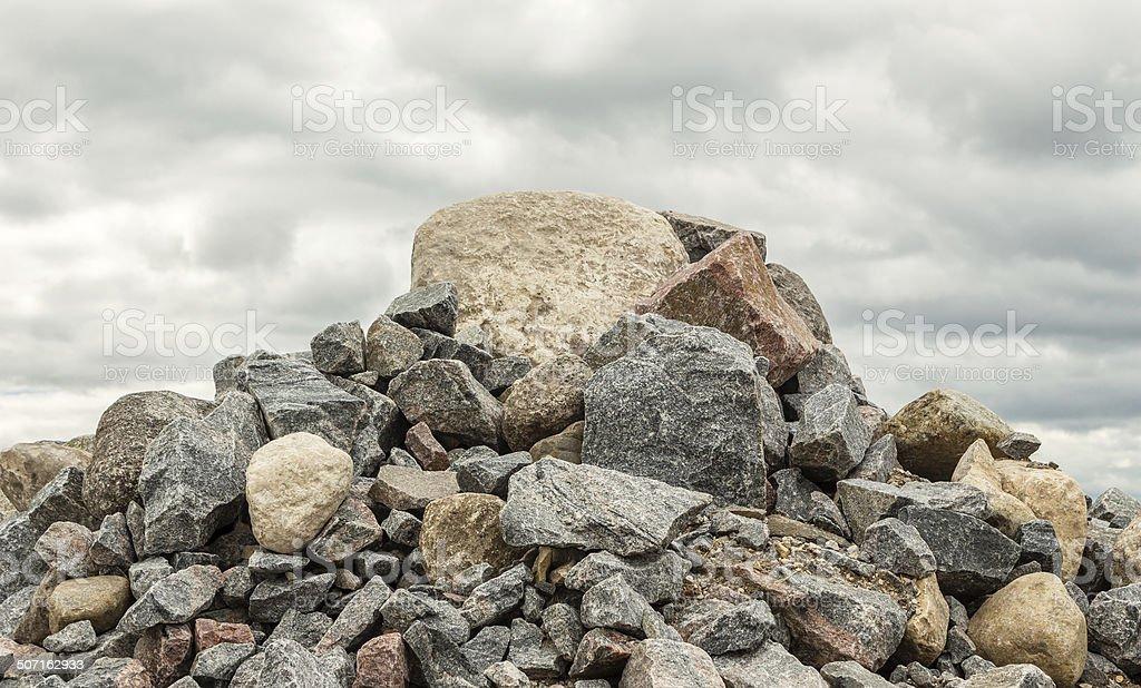 pile of huge rocks and boulders under dark grey sky stock photo