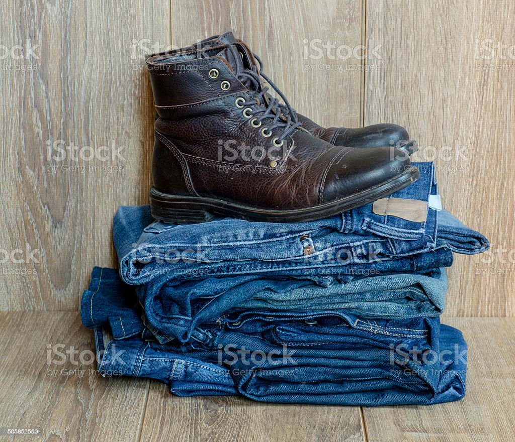 pile of jeans and boots stock photo