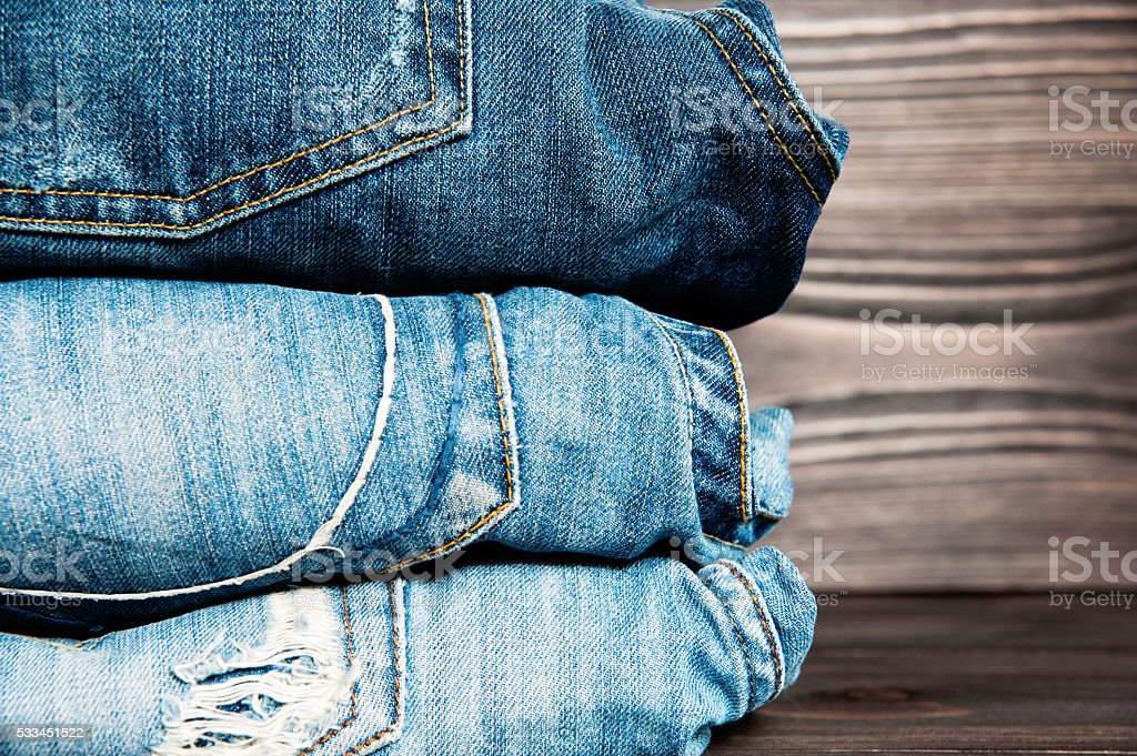 Pile of jeans clothes on wooden background. stock photo