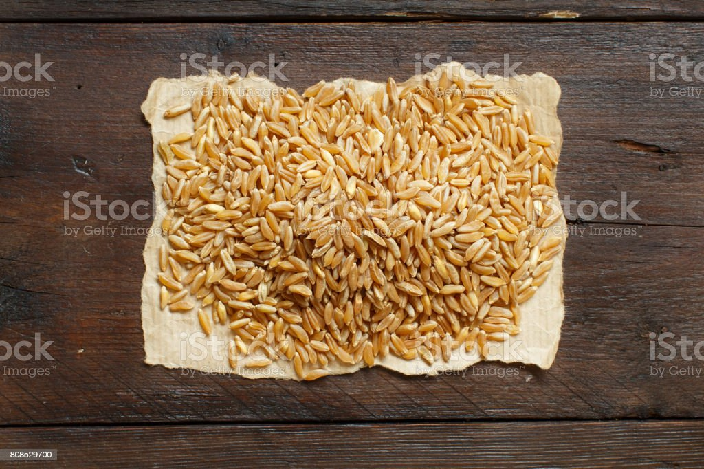 Pile of Kamut grain on wooden background stock photo
