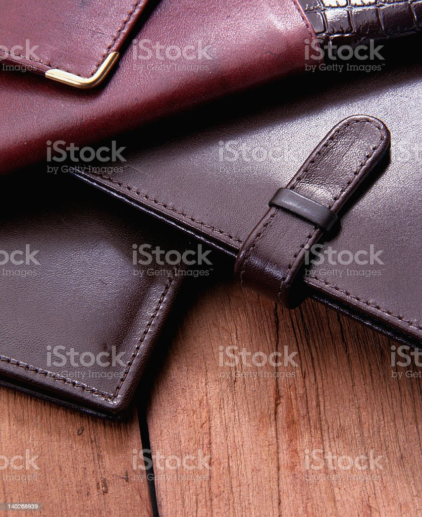 A pile of leather cases on a wooden table stock photo