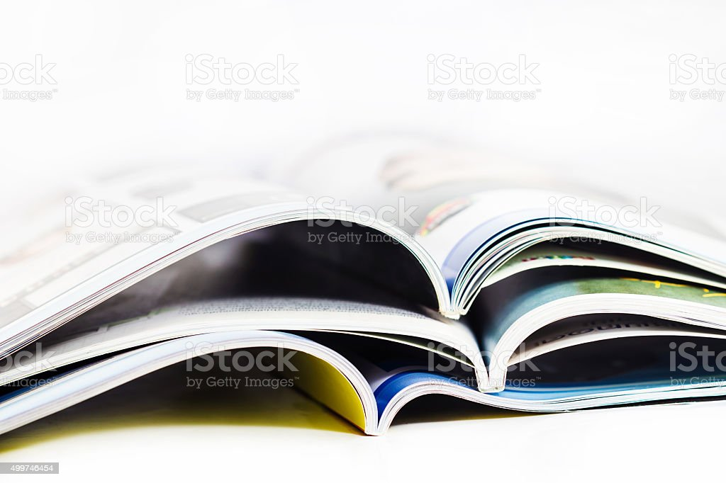 pile of magazines close up on white background stock photo