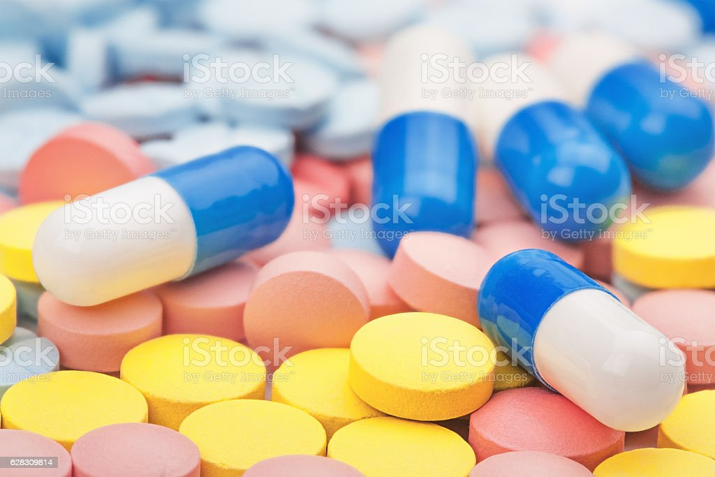 Pile of medical tablets and pills in different colors stock photo
