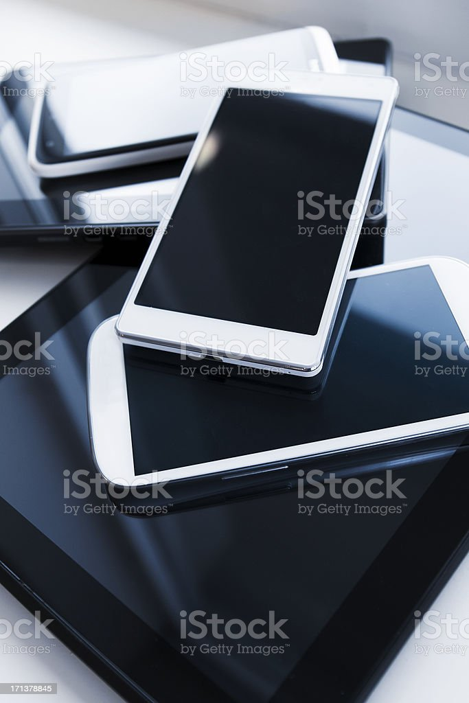 A pile of mobile phones and digital tablets stock photo