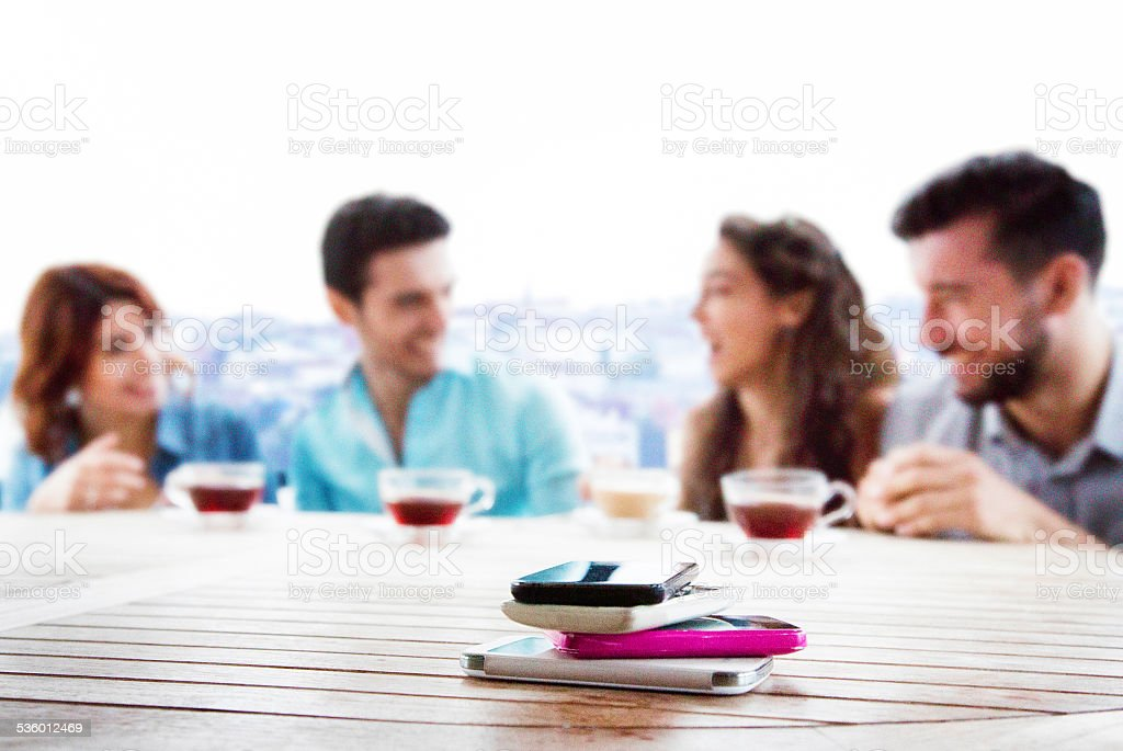 Pile of mobile phones with friends having fun in background stock photo