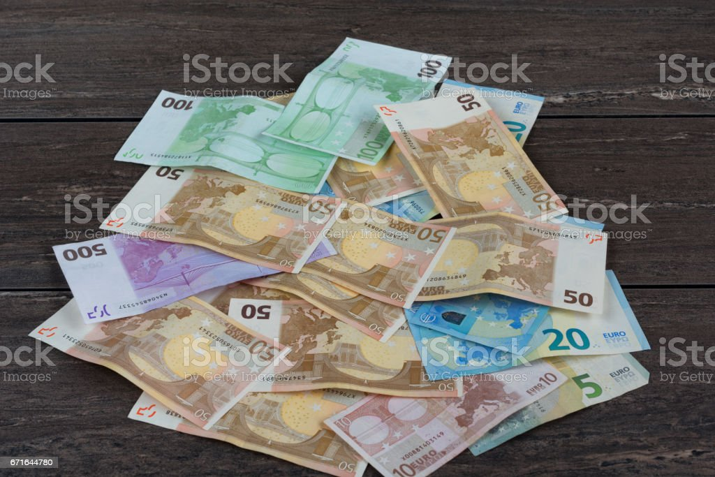 Pile of money on grey wooden board. stock photo