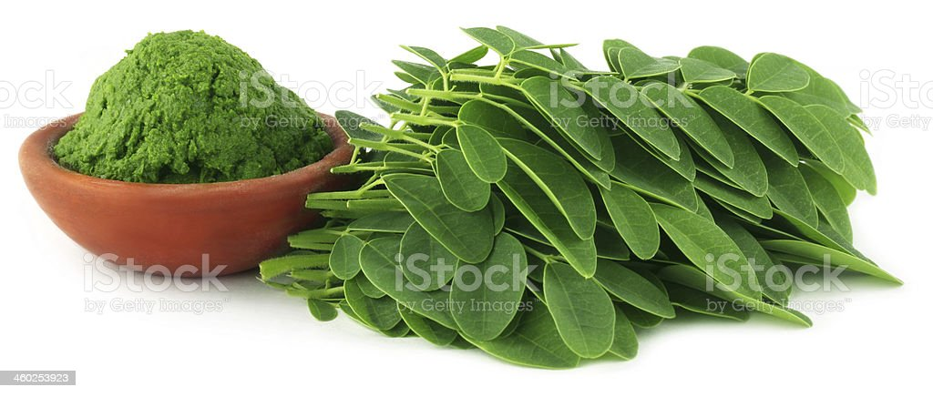 Pile of moringa leaves next to a bowl of green paste stock photo