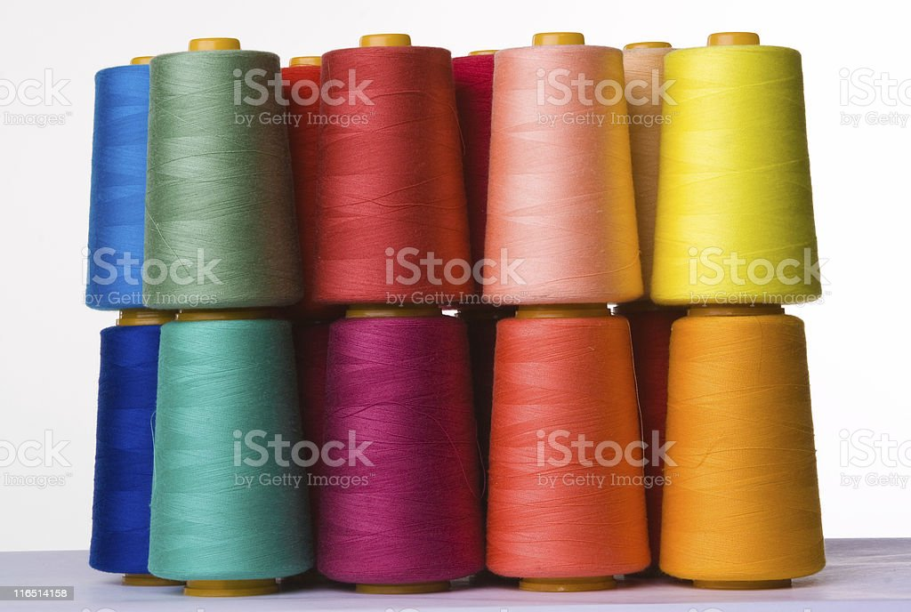 A pile of multicolored spools of sewing thread stock photo
