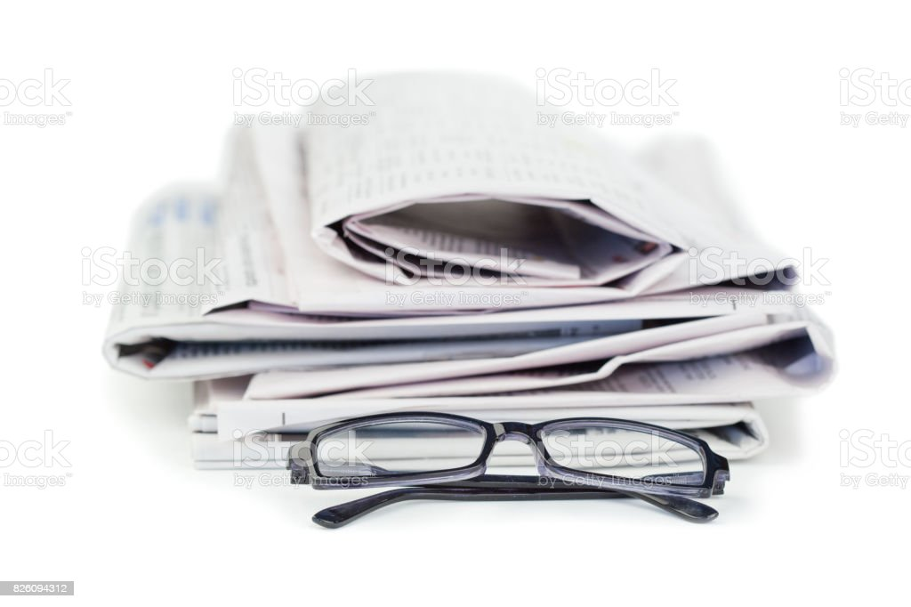 A pile of newspapers and a pair of reading glasses stock photo