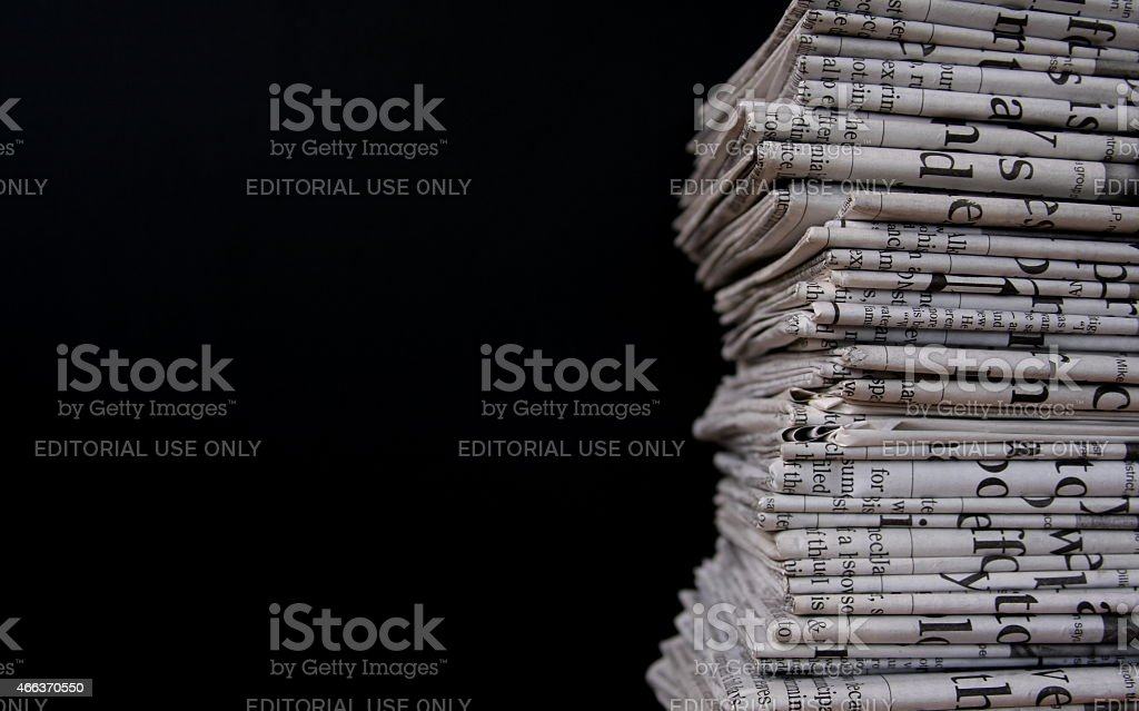 Pile of Newspapers on Black Background stock photo