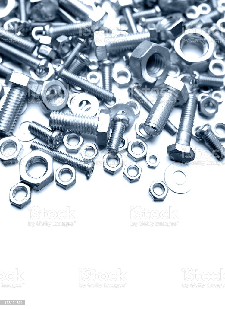 A pile of nuts and bolts at the top of a white background royalty-free stock photo