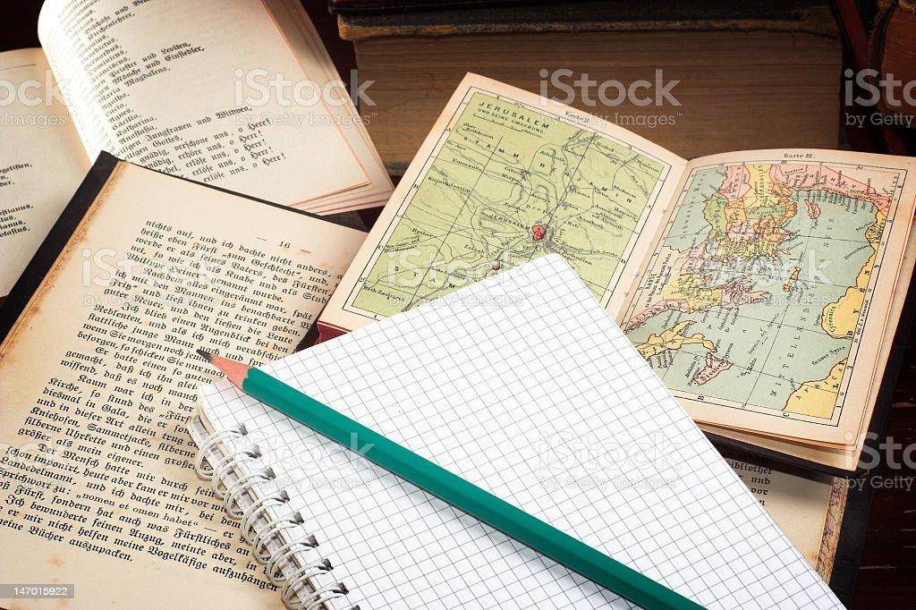 A pile of old books and a notebook sitting on top of a table stock photo