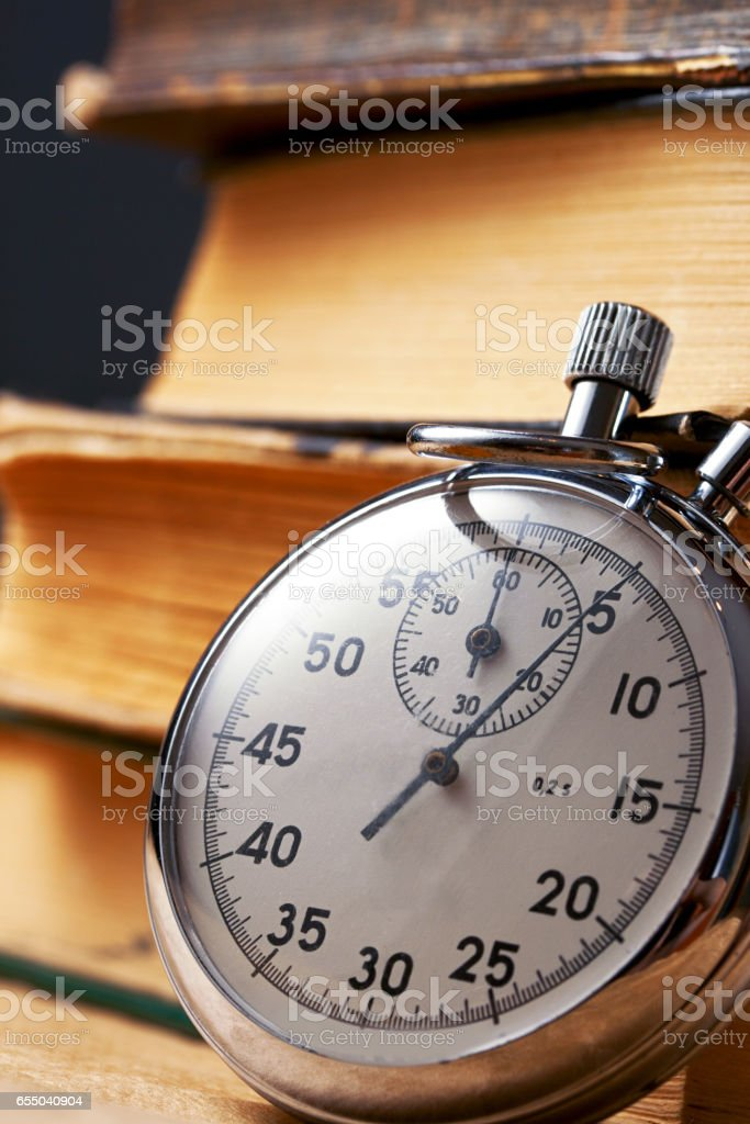 Pile of old books and stopwatch stock photo
