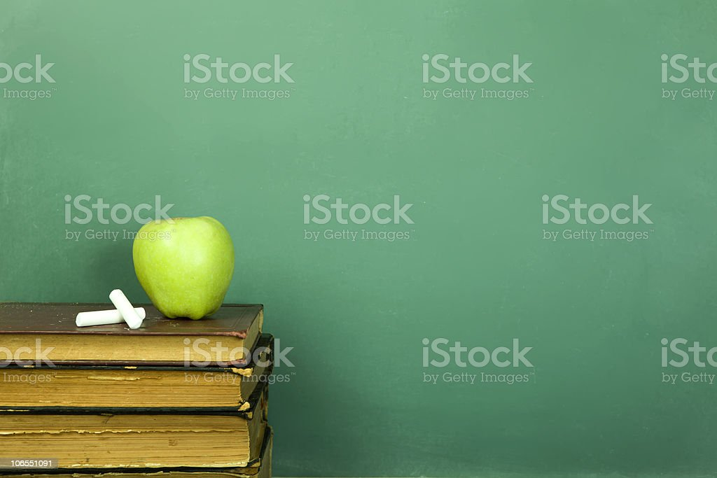 Pile of old books with green apple and chalk on top royalty-free stock photo