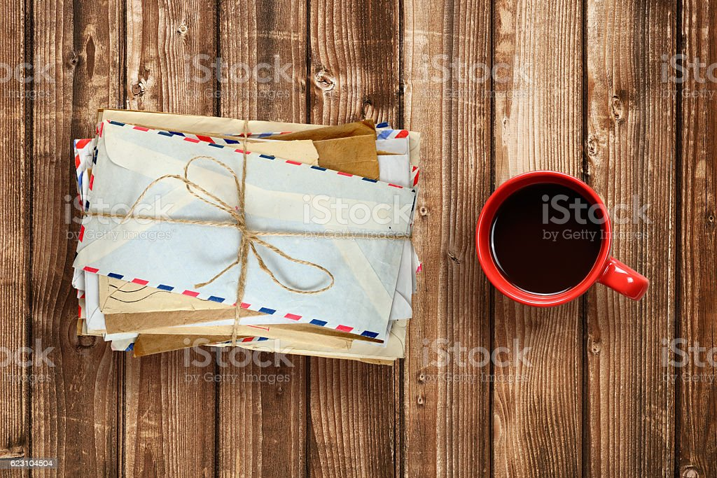 Pile of old envelopes and coffee cup on wooden table stock photo