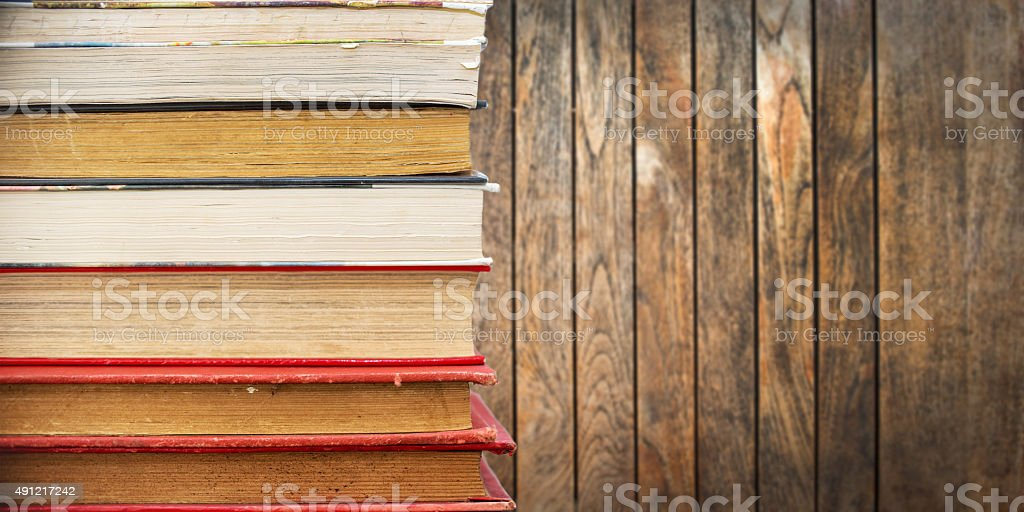 Pile of old vintage books, wooden planks background stock photo