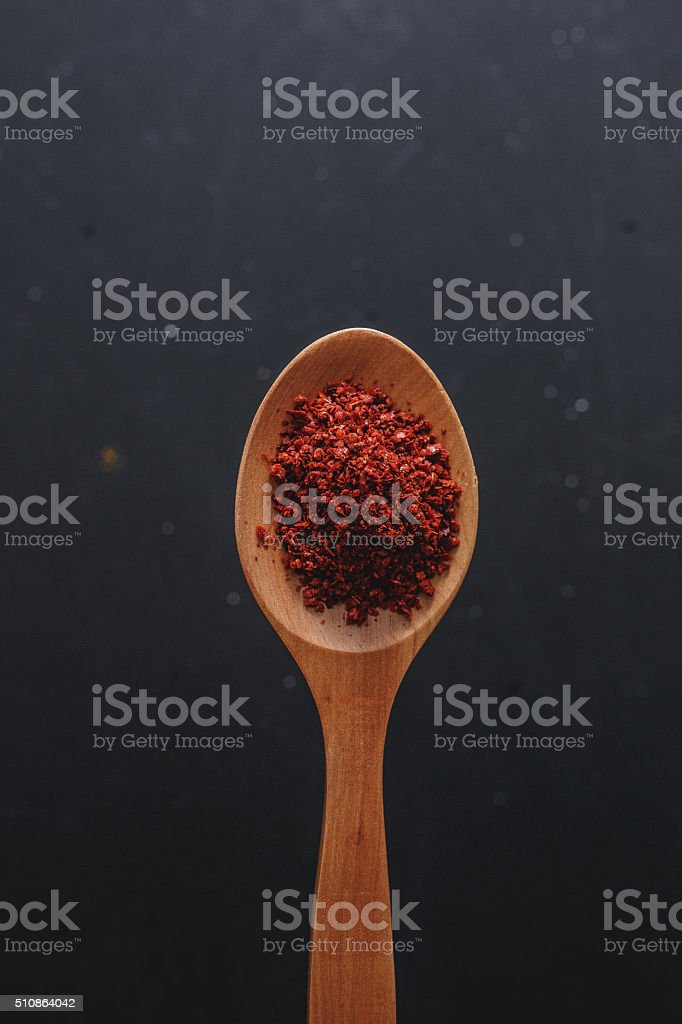 Pile of paprika powder in wooden spoon stock photo