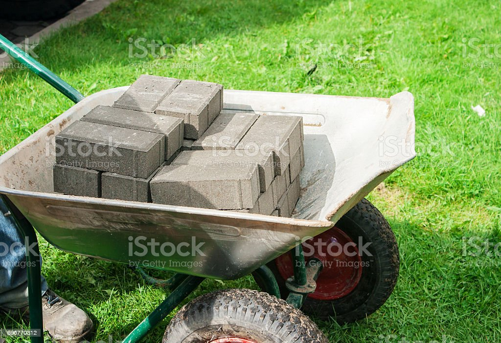pile of paving slabs lying in a wheelbarrow stock photo