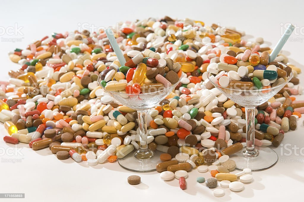 pile of pills and two drug cocktails stock photo