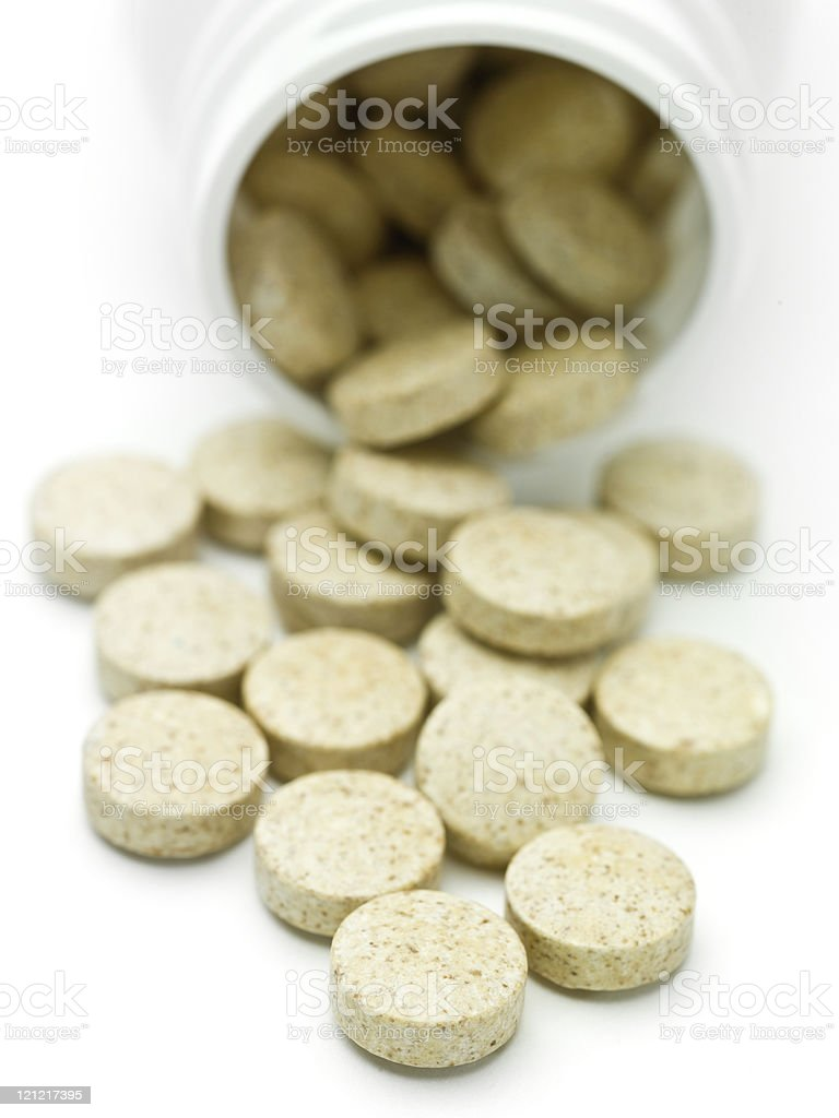 A pile of pills falling out of a tub on a white background royalty-free stock photo