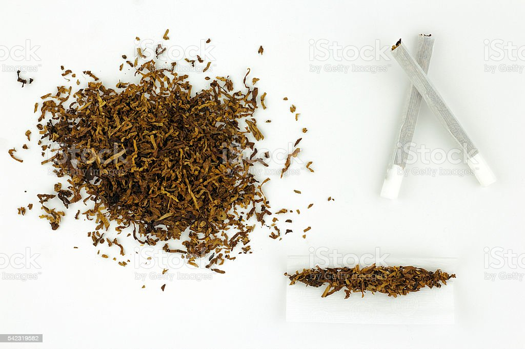 Pile of Pipe tobacco with rolled cigarettes and papers stock photo
