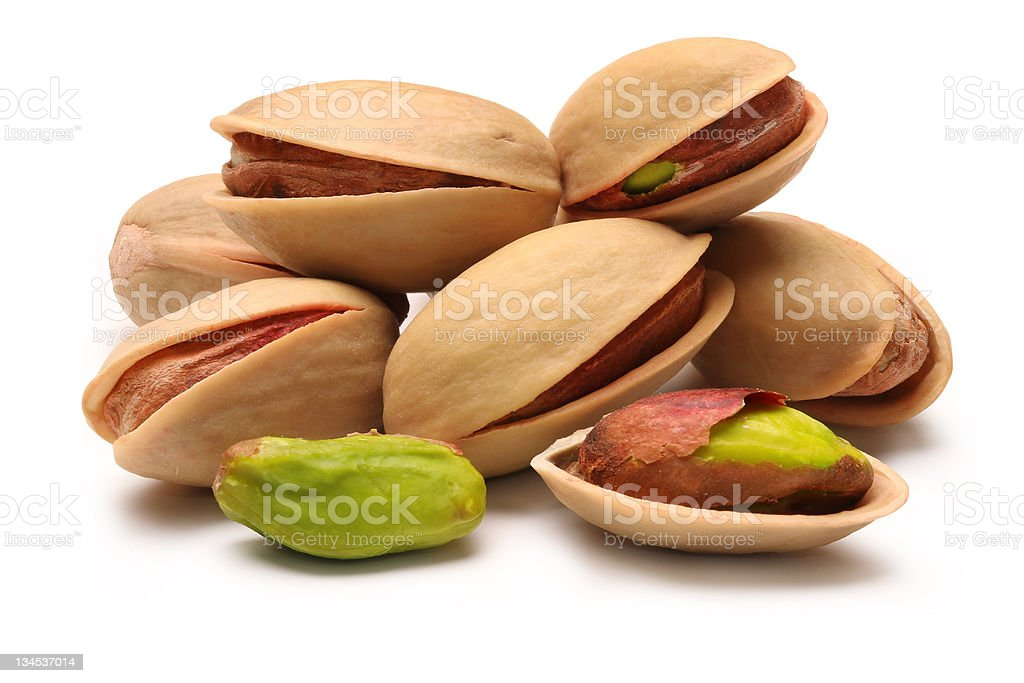 A pile of pistachio nuts on a white background stock photo