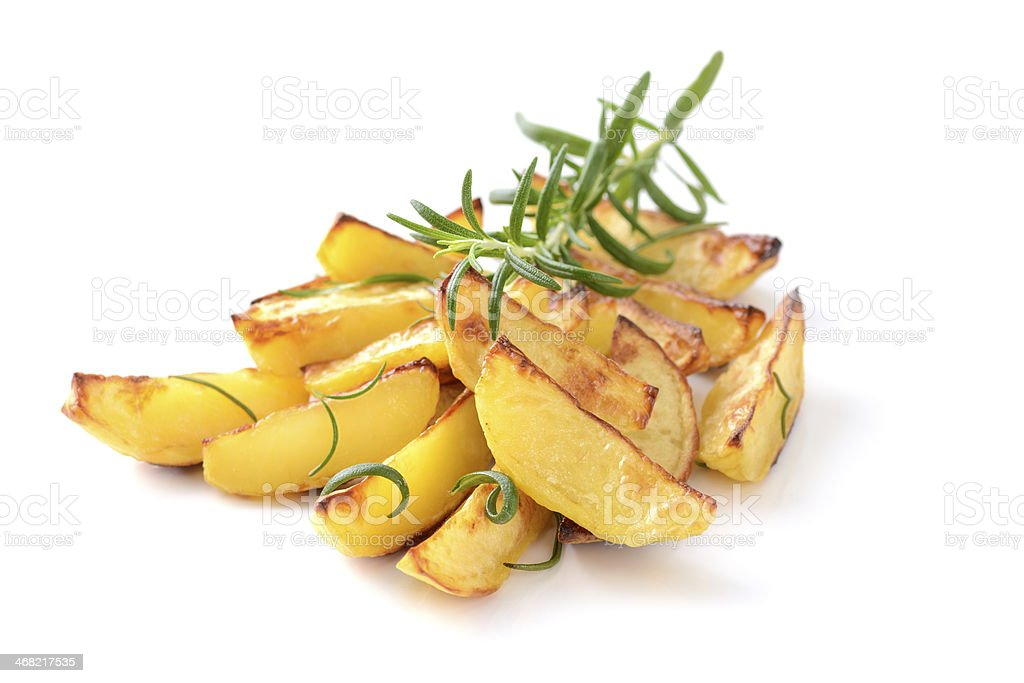 A pile of potato wedges with a green garnish on top stock photo