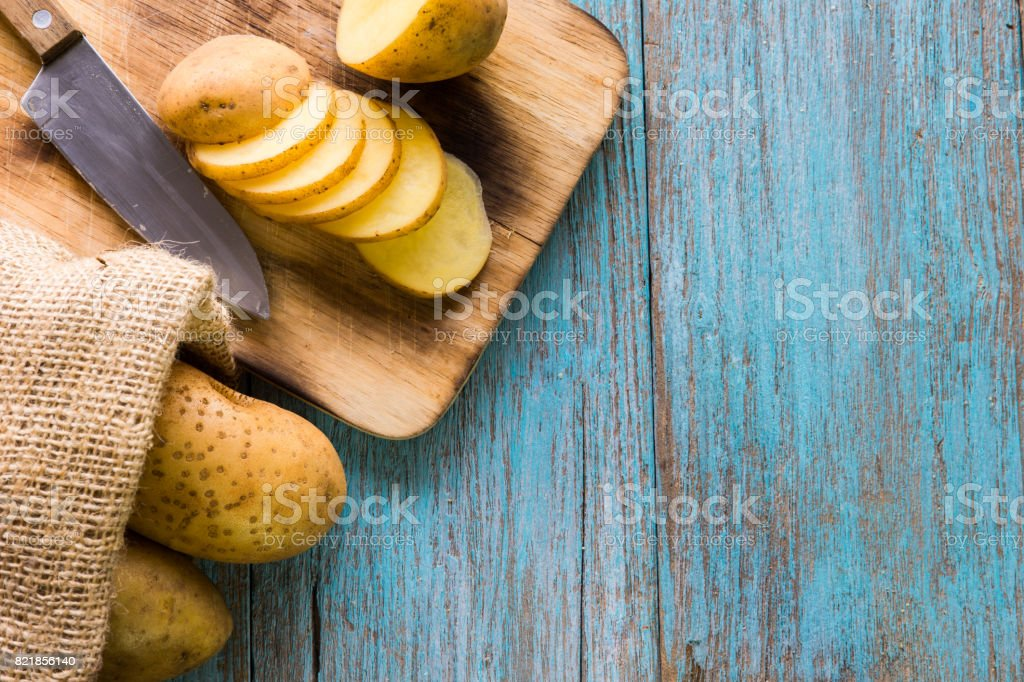 Pile of potatoes lying on wooden boards with a potato bag in the background stock photo
