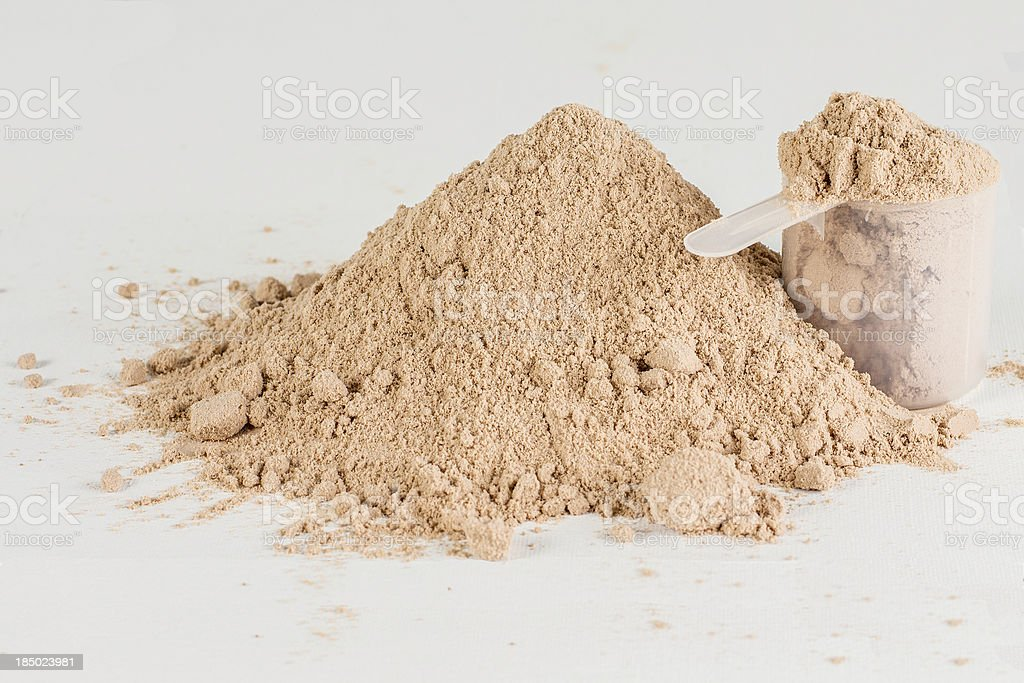 A pile of protein powder and a scoop stock photo