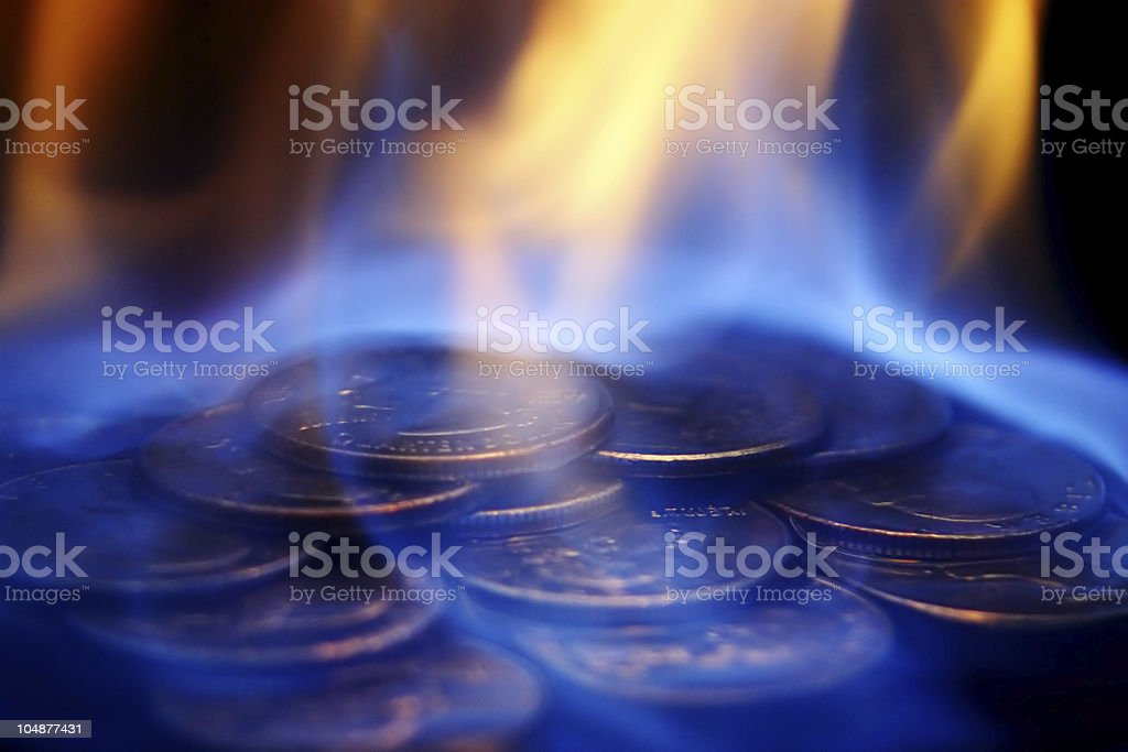 Pile of quarters on fire with blue and orange flames royalty-free stock photo
