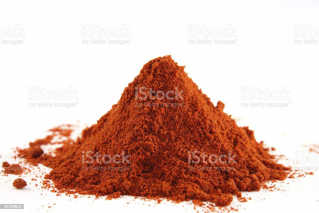 Pile of red ground paprika over a white surface stock photo